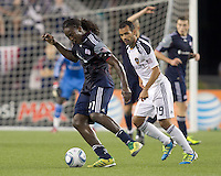 New England Revolution forward Shalrie Joseph (21) dribbles as Los Angeles Galaxy midfielder Juninho (19) defends. In a Major League Soccer (MLS) match, the Los Angeles Galaxy defeated the New England Revolution, 1-0, at Gillette Stadium on May 28, 2011.