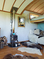 A small sofa strewn with a variety of cosy sheepskins and located close to the wood-burning stove, serves as the living area beneath the sleeping platform
