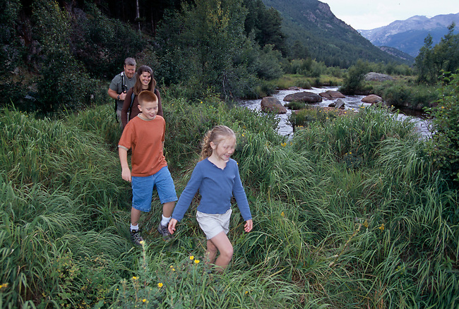Family of four hiking verdant trail along Big Thompson River, Moraine Park, Rocky Mtn Nat'l Park, CO