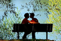 Austin Fortune of Anderson leans in to kiss Danielle Beecher of Williamston on a shady bench overlooking the pond at Chris Taylor Memorial Park Friday.