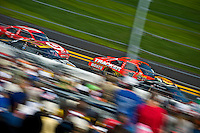 Drafting partners Jamie McMurray (#1) and Juan Pablo Montoya (#42) race past the grandstand.