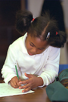 Girl age 6 writing at Youth Express Christmas party.  St Paul  Minnesota USA