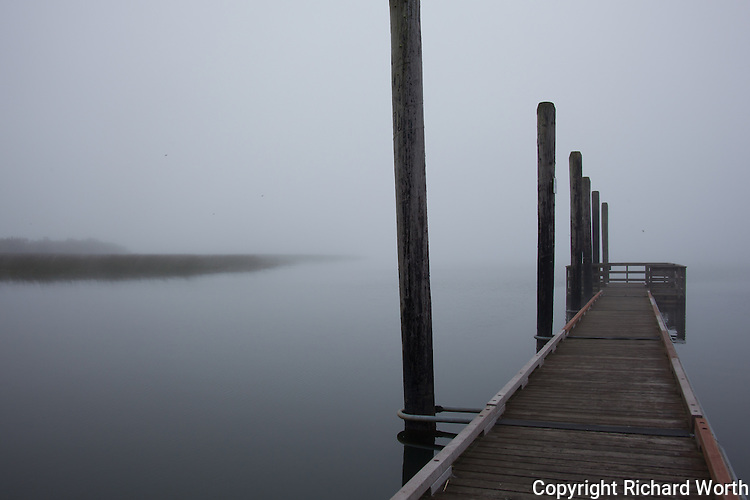 A boat launch site's dock  begs to be metaphor when it is surrounded by predawn fog with a hint of  'opposite shore' to one side.  Siltcoos Lake, Oregon.