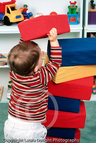 18 month old toddler boy stacking large foam blocks vertical