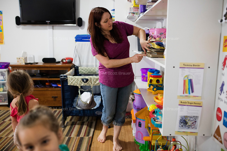 Lora Reyes is a licensed family childcare educator in Westfield, Mass., where she operates the daycare Lora's Little Ones out of her home on Thurs., June 2, 2016. Here she gets activities ready for children after breakfast; activities included card making, puzzles, and pretend activities. Today she was in charge of 7 children, aged 14 months to 5 years old, handling meals, playtime, and educational activities throughout the day, starting about 7am and going until 4:30pm. She uses the Mother Goose Time curriculum throughout the day. Reyes is currently pursuing an undergraduate degree in Psychology at Holyoke Community College. She started 2 years ago after earning a Child Development Associate certification.