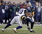 St. Louis Rams safety Darian Stewart, left, looses his helmet while tackling Seattle Seahawks wide receiver Ben Obomanu at  CenturyLink Field in Seattle, Washington on December 12, 2011. The Seahawks beat the Rams 30-13. ©2011 Jim Bryant Photo. All Rights Reserved.