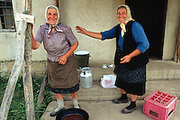 Kosovo. Village of Gaglavica. Two old serb women, both farmers, laugh together. Two cups, a milk canister, a bucket and a plastic crate are lying on the concrete ground. Kosovo (Albanian: Kosova) is a province of Serbia. While Serbia's sovereignty is recognised by the international community, in practice Serbian governance in the Kosovo province is virtually non-existent.  © 1995 Didier Ruef