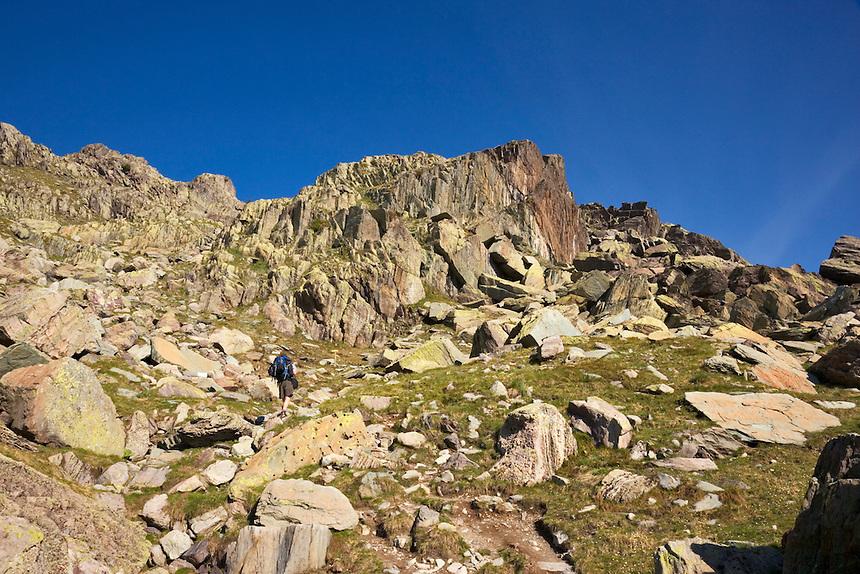 Parc National du Mercantour.  Hiker walks on track through the Vallee des Merveilles, GR52, Alpes-Maritimes, Provence, France. Model released.
