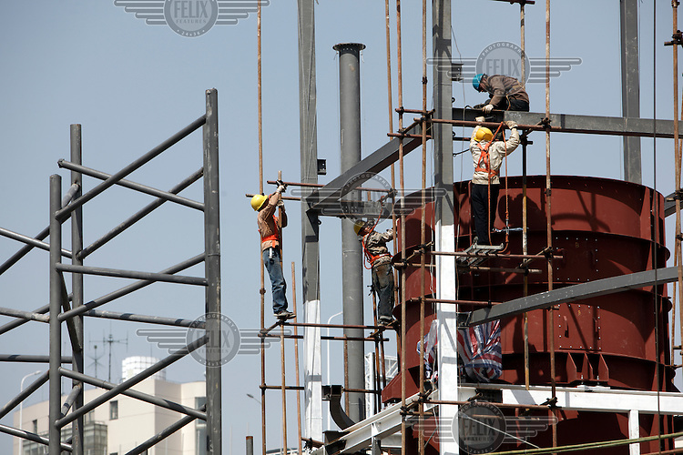 A construction crew work to erect steel girders for the Latvia Pavilion at the 2010 World Expo site.