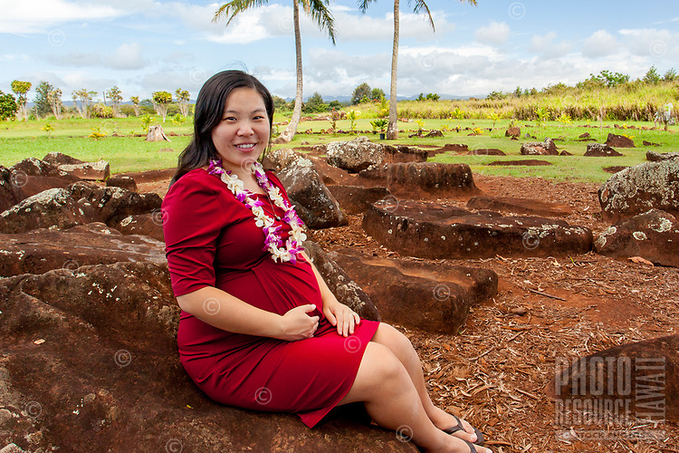 A young pregnant Asian woman sits on a large stone with a wish to receive a blessing at the sacred and historical Kukaniloko Birthstones State Monument, Wahiawa, O'ahu.