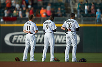 (L-R) Charlotte Knights outfielders Adam Engel (11), Luis Robert (9), and Paulo Orlando (16) stand for the National Anthem prior to the game against the Gwinnett Braves at BB&T BallPark on July 12, 2019 in Charlotte, North Carolina. The Stripers defeated the Knights 9-3. (Brian Westerholt/Four Seam Images)