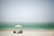 A girl sits under the shade of a beach umbrella to enjoy a book on a Dominican Republic beach