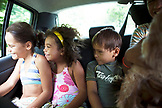 FRENCH POLYNESIA, Moorea Island. Kids riding in the back of a car with a dog.