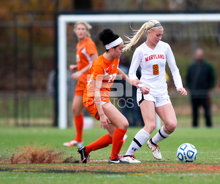 Ashley Spivey (8) of Maryland carries the ball away from Ally Andreini (27) of Miami during the game at Ludwig Field in College Park, MD.  Maryland defeated Miami, 2-1, in overtime.