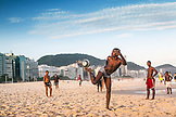 BRAZIL, Rio de Janiero, a group of friends juggle a soccer ball on Copacabana Beach