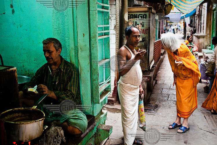 A foreigner dressed like a sadhu (holy man) looks for a street while a man is seen drinking his tea in the narrow alleys of the ancient city of Varanasi.