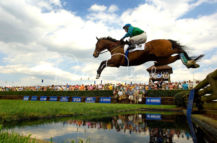 Low angle view of the crowd as a horse jumps over a pool of water during the Queen's Cup Steeplechase in Mineral Springs, NC.