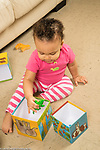 12 month old baby girl at home playing with toy animals and cardboard blocks, putting toy inside container, concept inside