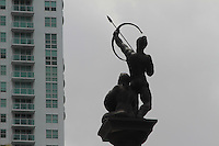 an archer statue pointing his arrow up at the window of a newly risen condo building