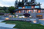 Outdoor lighting illuminates the entry to this newly landscaped home in the Pacific Northwest.