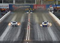 Feb 21, 2015; Chandler, AZ, USA; NHRA funny car driver Cruz Pedregon (left) races alongside Ron Capps during qualifying for the Carquest Nationals at Wild Horse Pass Motorsports Park. Mandatory Credit: Mark J. Rebilas-