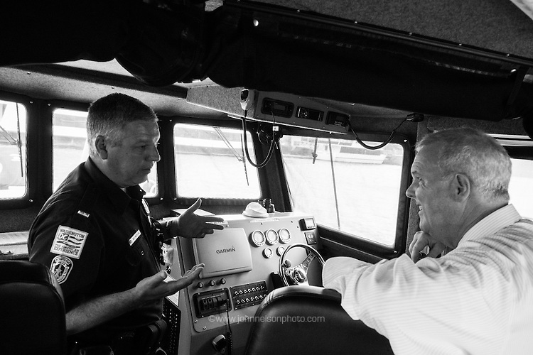 Lt Paul Niepling of the Washington Metro Police Department gives council member Tommy Wells a tour of the harbor patrol facilities.