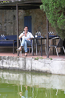 Estelle Daure, of the owner family by the pond at the restaurant. Chateau de Jau, Cases de Pene, Roussillon, France