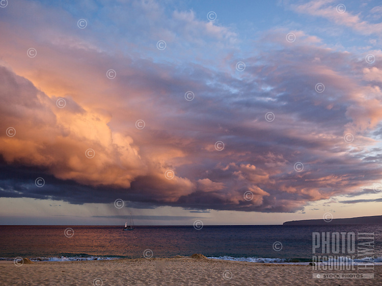 Makena beach with sailboat and big peach-colored sunset clouds on Maui.