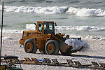 Tourists and locals along Pensacola Beach were seen watching the work of heavy equipment working around-the-clock, day and night trying keep up with the battle of the arriving oil. Loaders carry off bags of oil and tar balls collected by overnight workers while a line of defense was being laid at the waterline in an attempt to capture the beach staining oil film.