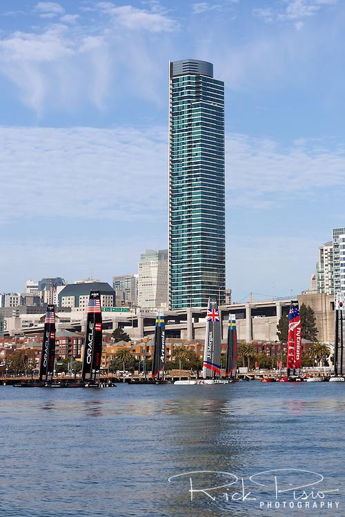 America's Cup racing boats at anchor along the San Francisco waterfront.