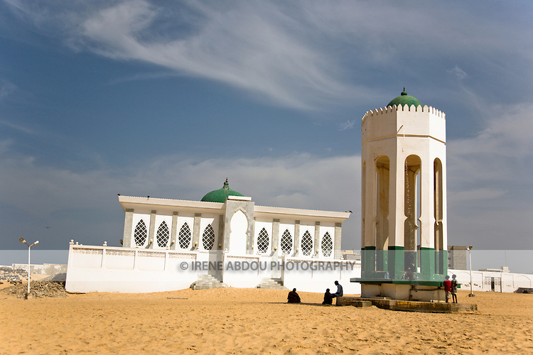 """The Seydina Limamou Laye Mausoleum sits on the coast of Senegal in the fishing village of Yoff.  Seydina Limamou Laye (1843-1909) was the founder of the Layène (meaning """"partisans of God"""") brotherhood.  In front of the mausoleum, children wash at the well of Diamalaye (zem-zem holy water)."""