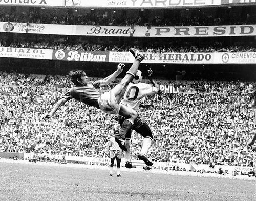 Italian defender Tarcisio Burgnich (L) performs a bicycle kick in his attempt to clear the ball from Brazilian star forward Pele during the 1970 World Cup final Brazil against Italy at Aztec Stadium in Mexico City, Mexico on 21 June 1970. Brazil won the game by a score of 4-1 against Italy and won the World Champion title for the third time.