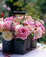 Detail of cut roses and dahlias in a chicken wire basket