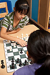 Afterschool chess program for elementary students graduates of Headstart program two girls playing