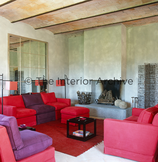 The simple contemporary fireplace is the main feature of  the colourfully furnished living room