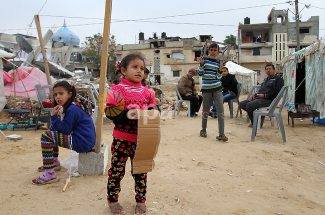 Palestinian children play outside tents near the ruins of their houses which witnesses said were destroyed by Israel shelling during a 50-day conflict last summer, east of Khan Younis in the southern Gaza Strip January 27, 2015. The main U.N. aid agency in the Gaza Strip said on Tuesday a lack of international funding had forced it to suspend payments to tens of thousands of Palestinians for repairs to homes damaged in last summer's war. Robert Turner, Gaza director of operations for the United Nations Relief and Works Agency (UNRWA), said in a statement that UNRWA received only $135 million of the $720 million pledged by donors to its cash assistance program for 96,000 refugee families whose homes were damaged or destroyed in the 50-day conflict between the Hamas Islamist movement and Israel. Photo by Abed Rahim Khatib