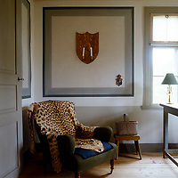In an otherwise austere country study an exotic note is struck by a leopard skin rug flung over an antique armchair