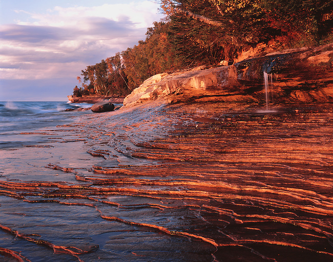 Sunset light lights up sandstone edges wetted by the Lake Superior waves on the shore beneath a small waterfall at Picturerd Rocks National Lakeshore in Alger County, Michigan.