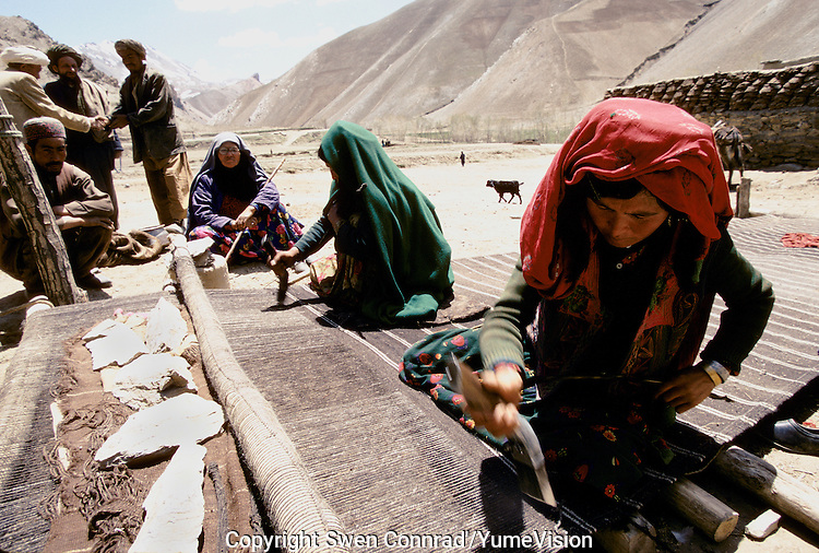 Two womans working on a kilim carpet at  Sabznaw village between Yakawlang an Pandjab. Hazarajat, Afghanistan.