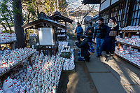 "Asian tourists take photos of the large collection of ""Lucky Cat"" statues at Gotokuji Temple in Gotokuji, Satagaya, Tokyo, Japan. Friday January 11th 2019. Gotoikuji Temple is famous as the supposed birthplace of the ""maneki neko"" or  ""beckoning cat"", which is a small white cat with one paw raised that is considered a lucky charm bringing customers and money into a business."