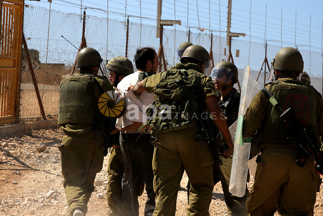 An Israeli soldier detains a demonstrator during a protest against the controversial Israeli barrier in the West Bank village of Bilin near Ramallah on Sep 25, 2009. Photo by Issam Rimawi