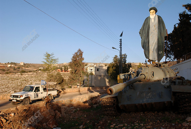 For the attention of foreign pix-A cut out image of the Ayatollah Khomeini, the former head of Iran, stood on a disused tank close to the border between Lebanon and Israel as a UN troops, who observe the military situation on the border, drover past.<br />