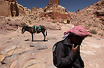 A young Bedouin who guides tourists through the archaeological site of Petra in Jordan. Petra is the most visited tourist attraction in Jordan, a symbol of the country for its historical and archaeological importance. It has been a UNESCO World Heritage Site since 1985. The Bedouin families that have been living for centuries in the caves of Petra, agreed to move out into a small village, built near the site of Petra. Most of them earn their living from tourism which seems to be the only option available, especially for the younger generations.