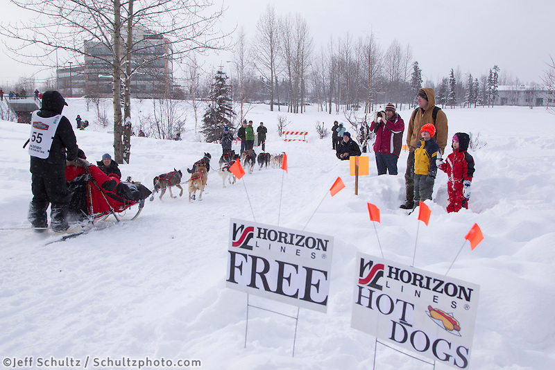 Josh Cadzow runs past a sign for free hotdogs courtesy of Horizon Lines along the bike trail near the Alaska Native hospital during the Ceremonial Start of Iditarod 2012 in Anchorage, Alaska.