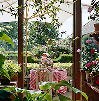 View through the open door of the greenhouse to a table laid for lunch in the garden under a white canvas umbrella
