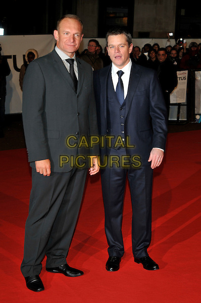 "FRANCOIS PINEAAR & MATT DAMON .Attending the ""Invictus'"" UK Film Premiere at the Odeon West End cinema, Leicester Square, London, England, January 31st, 2010..arrivals full length black grey gray tie suit navy blue waistcoat.CAP/PL.©Phil Loftus/Capital Pictures"