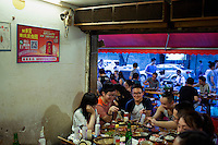 People eat at Gang Shan Zha Zha, a popular streetside hotpot restaurant on Tiyu Road in central Yuzhong distrist, Chongqing, China.<br /> <br /> The restaurant sits on the site of a former neighborhood garbage collection point and &quot;zha zha&quot; is local slang for &quot;garbage.&quot; The restaurant has been open for 5 years and recently opened a second location elsewhere in Chongqing. A manager of the restaurant said that they server 60-70 tables every night, with many tables' bills coming to over 1000RMB. The restaurant often has a long wait. The site is well-reviewed on online restaurant sites similar to Yelp and is known for having good flavor, serving fresh food, and being clean.