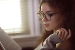 Portrait of a young woman in glasses reading a book by the window in sunlight