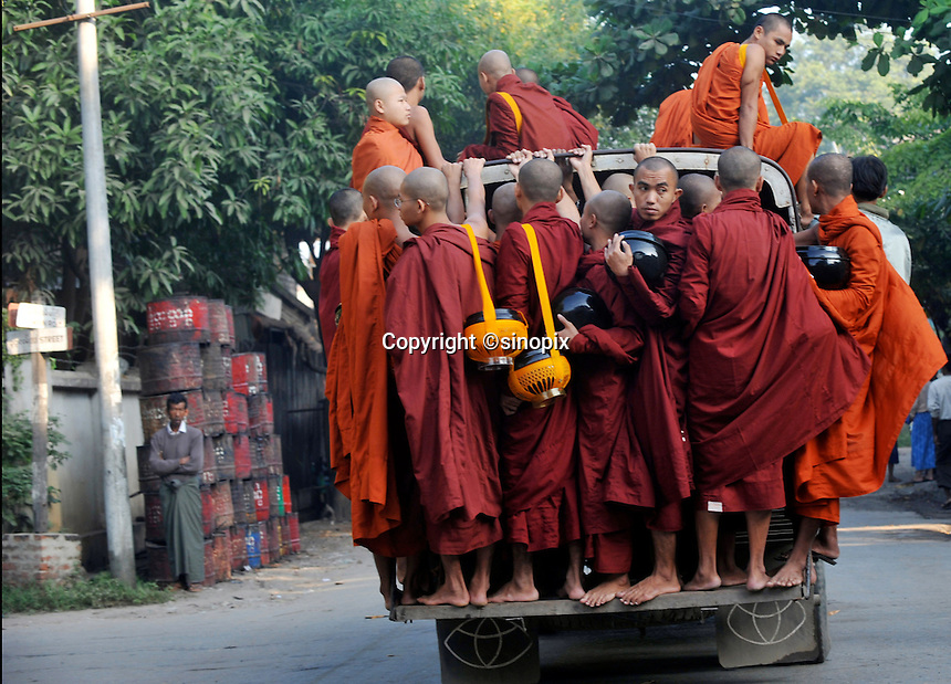 "Monks ride a bus, early morning, on the way to beg for food from villagers in Mandalay, Burma Oct 08.  Monks in this largely Buddhist country have to beg from villagers in order to feed themselves and in this city the government hand-outs stopped after the ""saffron revolution"" of October 2007.<br />