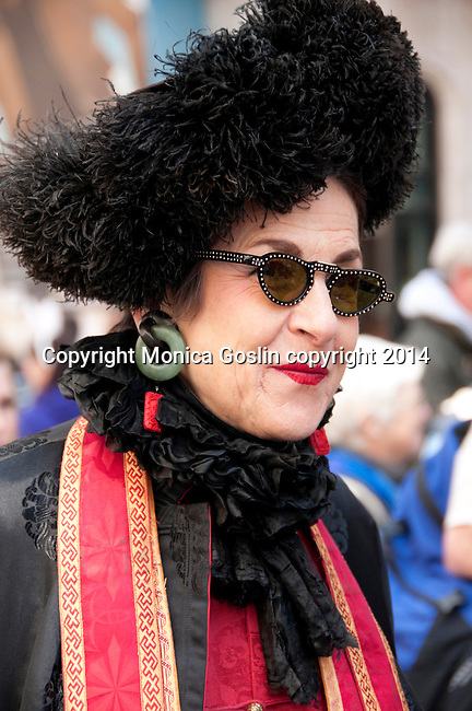 Woman wearing a black and red outfit and a large black feather hat in the Easter Parade on 5th Avenue in New York City